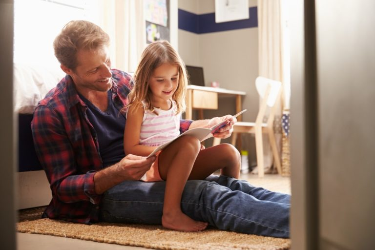 child reading book with her father