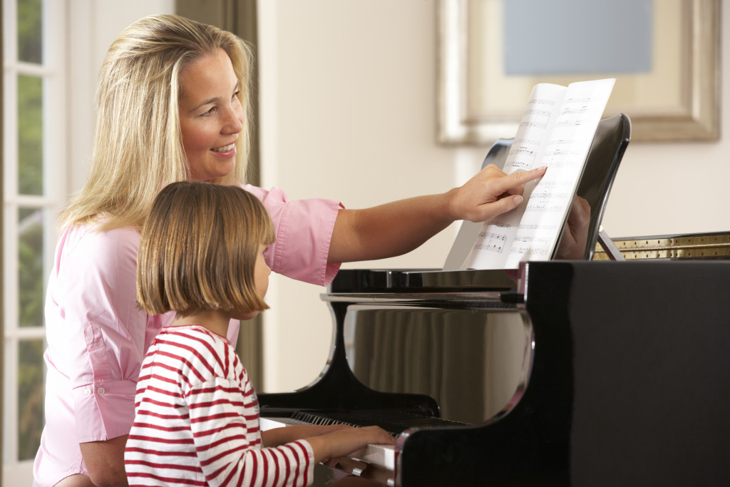 Young girl playing piano in music lesson